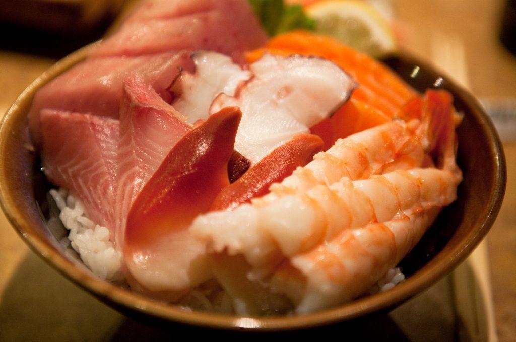 Plato de chirashi sushi, arroz cocido con pescado crudo encima (gambas, salmón, pulpo, atún)